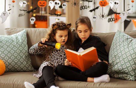 girls in halloween costumes reading book at home