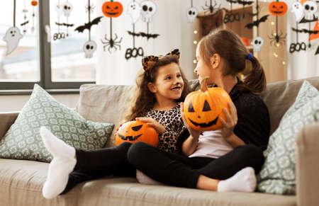girls in halloween costumes with pumpkins at home Zdjęcie Seryjne