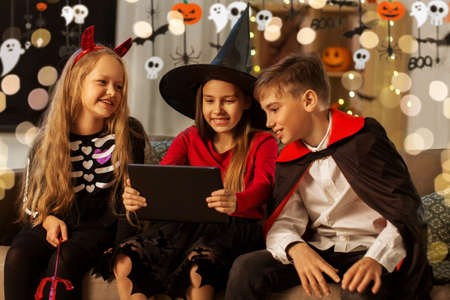kids in halloween costumes with tablet pc at home