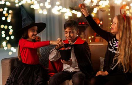 kids in halloween costumes sharing candies at home Zdjęcie Seryjne
