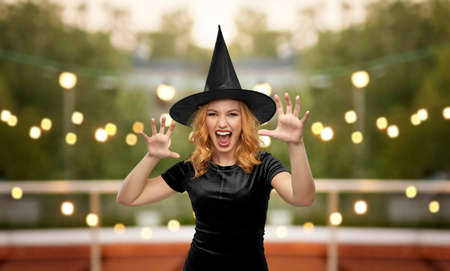 scary woman in black halloween costume of witch