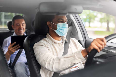 passenger with tablet pc and car driver in mask