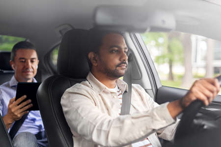 indian male driver driving car with passenger