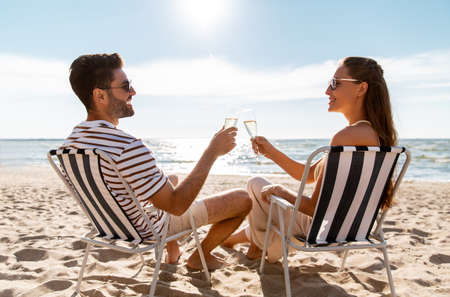 happy couple drinking champagne on summer beach