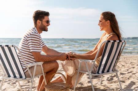happy couple sitting in folding chairs on beach Zdjęcie Seryjne