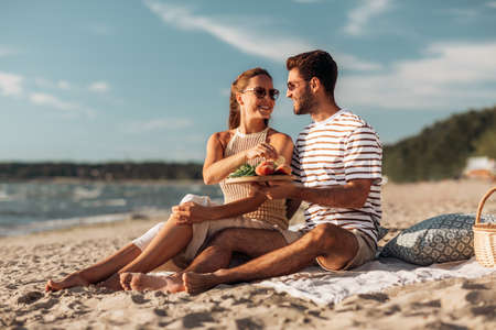 happy couple with food having picnic on beach