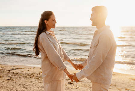 happy couple holding hands on summer beach