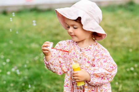 happy baby girl blowing soap bubbles in summer
