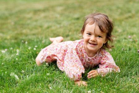 happy little baby girl lying on grass in summer