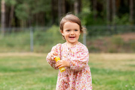 happy baby girl with soap bubble blower in summer