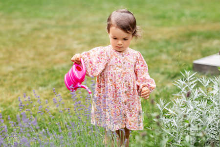 happy baby girl with watering can in summer garden Zdjęcie Seryjne