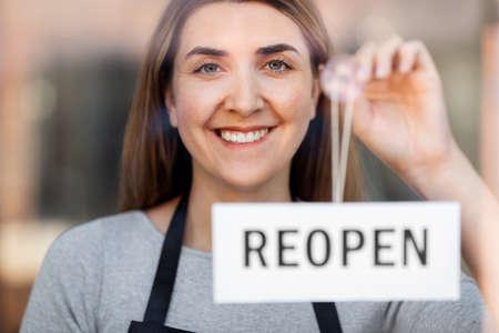 happy woman hanging reopen banner to door glass Zdjęcie Seryjne