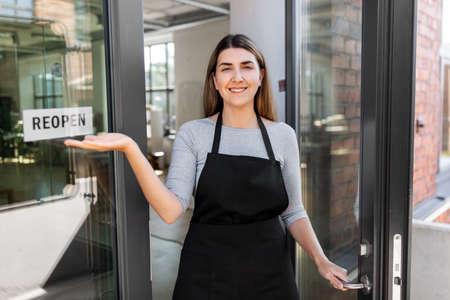 happy woman showing reopen banner on door glass