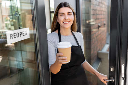 happy woman with coffee and reopen banner on door