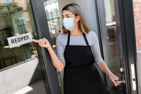 woman in mask showing reopen banner on door glass