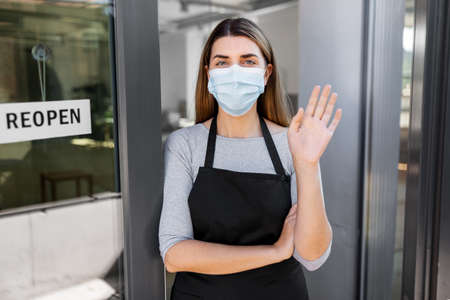 woman in mask with reopen banner on door glass