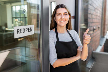 woman with reopen banner on door showing thumbs up Zdjęcie Seryjne