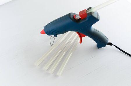 Blue glue gun and hot melt rods on white background.