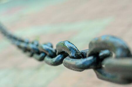Big links of dark metal chain in sity street, closeup.