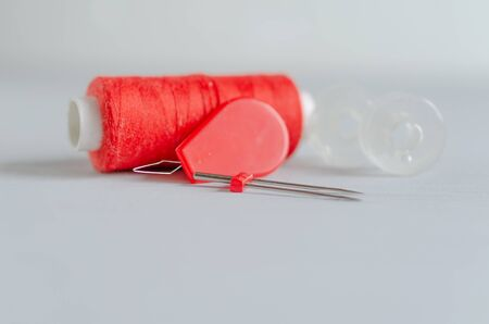 Red accessories for sewing on white background. Needlework and craft concept Stok Fotoğraf