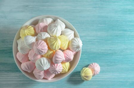 Meringues in a white bowl. Colorful delicious dessert. Top view. Reklamní fotografie