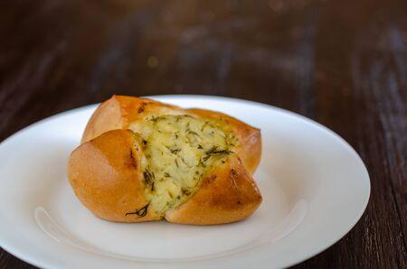Homemade buns in white plate on wooden background. 免版税图像