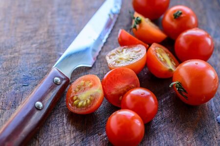 sliced cherry tomatoes and a sharp knife with a wooden handle on a dark background