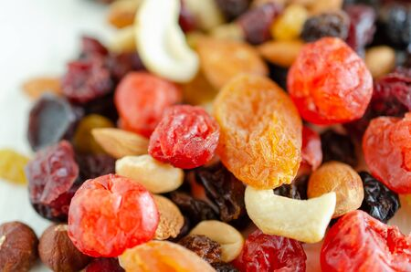 Mix of dried fruits and nuts close up background.