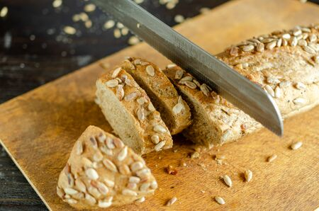 Fresh whole grain bread with kitchen knife on the kitchen. Healthy eating.