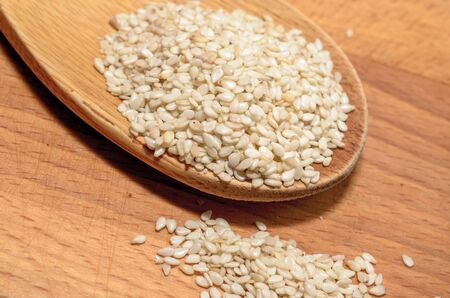 Organic natural sesame seeds on wooden spoon, healthy food background.