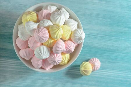 Meringues in a white bowl. Colorful delicious dessert. Top view. Stock fotó