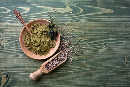 Composition with wooden bowl of hemp protein powder, cannabis seeds on wooden table. Space for text Stock Photo