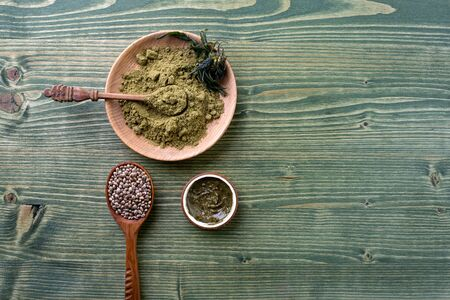 Composition with jar of hemp protein powder, cannabis seeds, organic cream on wooden table. Space for text