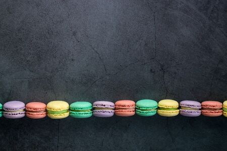 Colourful minimalistic greeting card concept. Different colours french macaroons on black grunge stone urban background. Poster for women, moms day, wedding invitation, birthday, Copy space, flat lay
