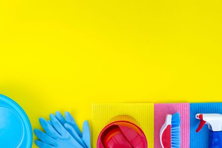 Colourful cleaning set for different surfaces in kitchen, bathroom and other rooms. Spring cleaning service vertical concept. Early spring regular clean up. Flat lay. Empty place for text or logo.