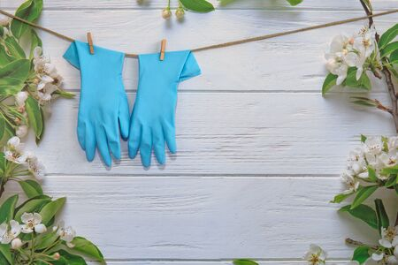 Rubber gloves, cleaning items on spring background, pastel wooden planks and spring blossoms. Close up. Spring regular cleaning. Flat lay. Empty place for text or logo. Banco de Imagens