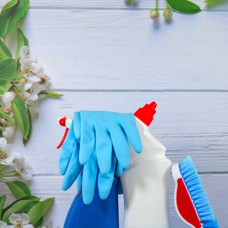 White bottle, spray, blue sponge, rubber gloves, cleaning set on spring background, pastel wooden planks and spring blossoms. Close up. Spring regular cleaning. Flat lay. Empty place for text or logo.