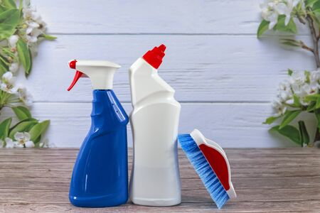 White bottle, spray, blue cleaning brush, cleaning set on spring background, pastel wooden planks and spring blossoms. Close up. Spring regular cleaning. Flat lay. Empty place for text or logo. Banco de Imagens