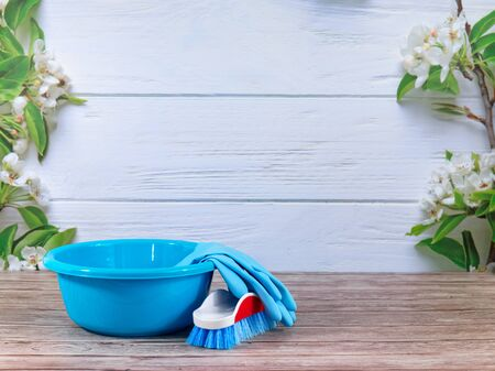 Blue washing up bowl, brush, blue rubber gloves, cleaning set on spring background, pastel wooden planks and spring blossoms. Close up. Spring regular cleaning. Flat lay.Empty place for text or logo. Banco de Imagens