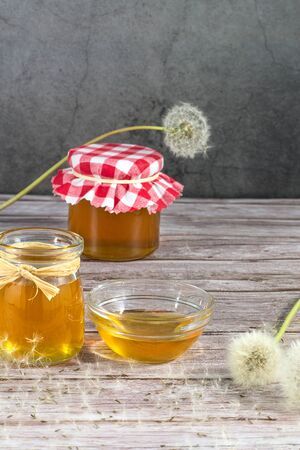 Dandelion jam, honey, jelly in a glass jar on a wooden table, black background with fresh flowers, dandelion airy seed heads, seeds, blow balls. Medicine, healthy food, health benefits from nature