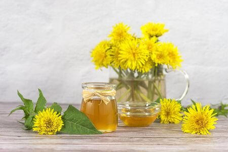 Dandelion jam, honey, jelly in a glass jar on a wooden table, white background with fresh yellow dandelion flowers. Medicine, healthy food, health benefits from nature Banco de Imagens