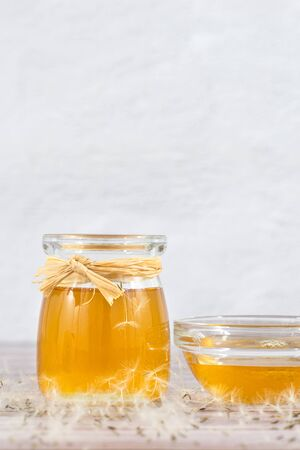 Dandelion jam, honey, jelly in a glass jar on a wooden table, white background with fresh flowers, dandelion airy seed heads, seeds, blow balls. Medicine, healthy food, health benefits from nature Banco de Imagens