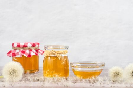 Dandelion jam, honey, jelly in a glass jar on a wooden table, white background with fresh flowers, dandelion airy seed heads, seeds, blow balls. Medicine, healthy food, health benefits from nature.