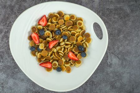 Pancake cereal. Trendy food, mini cereal pancakes in bowl on the table, grey cement background. Trendy baked mini pancakes with strawberries, blueberries . Copy space. Flat layout. Table top view.