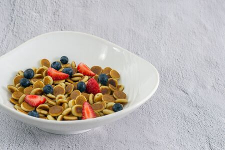 Pancake cereal. Trendy food, mini cereal pancakes in bowl on the table, cement vertical background. Trendy baked mini pancakes with spoon, strawberries, blueberries . Copy space. Flat layout