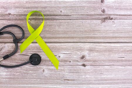 Mental health awareness concept. Lime green ribbon with mental health awareness text on old aged wooden background with stethoscope. May month green ribbon month to support mental health awareness