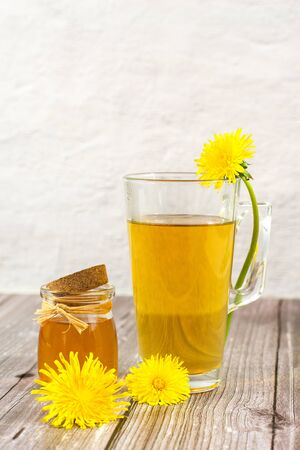 Dandelion tea and honey on wooden background. Transparent glass cup of hot healthy herbal tea with fresh yellow blossoms dandelions flowers. Herbal homeopathic medicine. Copy space for text Banco de Imagens