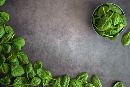 Raw fresh baby spinach leaves in bowl on grey background. Frame made of spinach background. Top view healthy leaf vegetable food on dark table.
