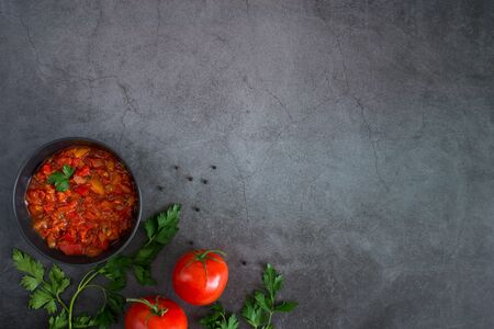 Traditional Latin American mexican salsa sauce, fresh tomatoes, parsley, pepper on black stone table.Tomato fresh sauce with red bell pepper, onion, olive oil, garlic, fresh basil. Top view copy space