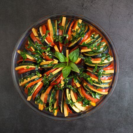 Ratatouille. Close up of traditional French stew of summer vegetables on table. Vegetarian stew made of zucchini, eggplants onions, garlic and tomatoes, aromatic herbs.Ratatouille casserole. Top view